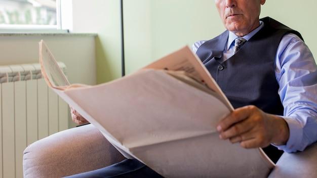 Homem negócios sênior, sentando, ligado, poltrona, jornal leitura