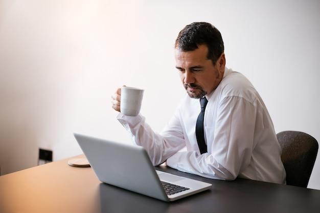 Homem negócios sênior, usando computador laptop, no trabalho