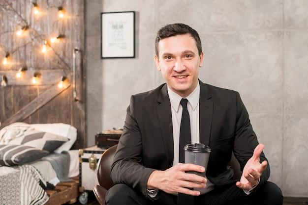 Homem negócios, sentando, com, xícara café, em, sala
