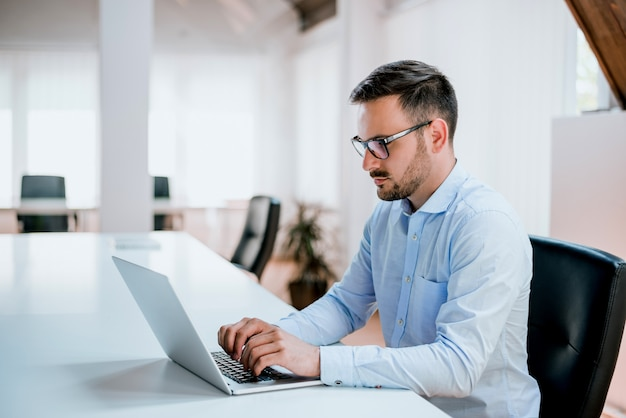 Homem negócios, sentando, em, escrivaninha escritório, trabalhar, computador laptop