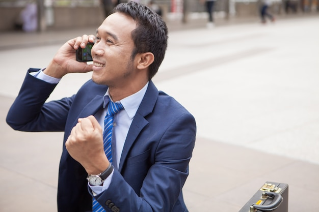 Homem negócios, sentando, ligado, escada, durante, callling, a, telefone, com, edifício escritório, fundo