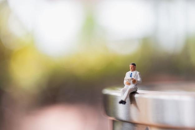 Homem negócios, sentando, livro leitura, ao ar livre