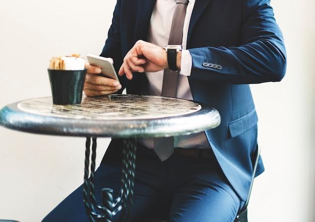 Homem negócios, sentando, tempo verificando, de, relógio pulso