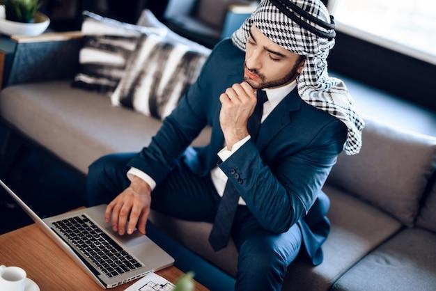 Homem negócios, sentar sofá, e, olhar, laptop