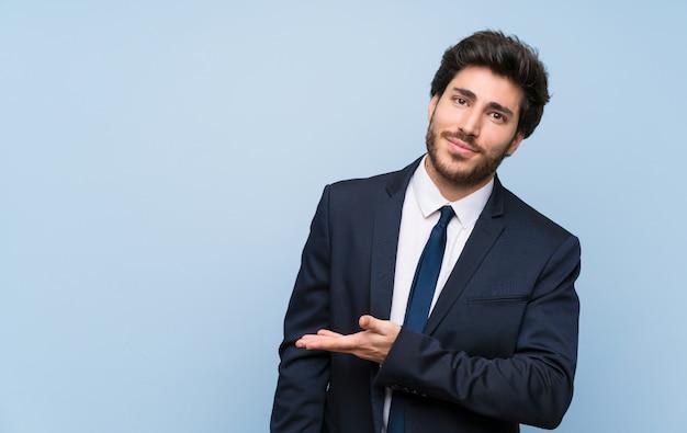 Homem negócios, sobre, isolado, parede azul, apresentando, um, idéia, enquanto, olhar, sorrindo, direção