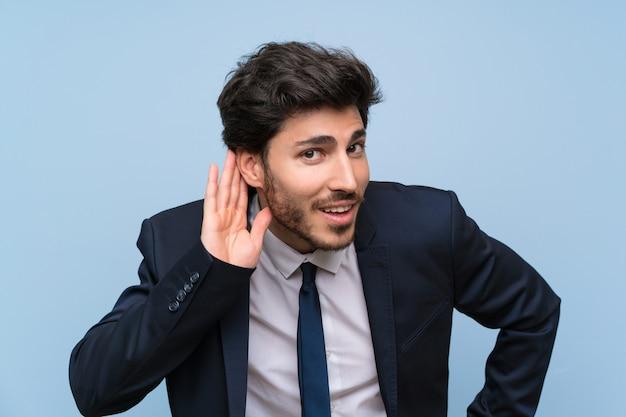 Homem negócios, sobre, isolado, parede azul, escutar, algo, pondo mão, ligado, a, orelha