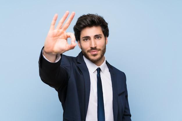 Homem negócios, sobre, isolado, parede azul, mostrando, tá bom sinal, com, dedos
