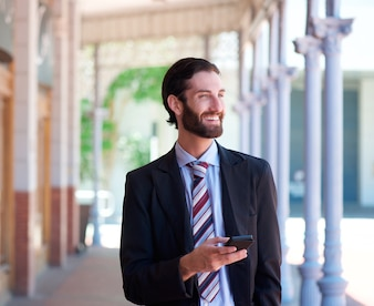 Homem negócios, sorrindo, ao ar livre, com, telefone móvel