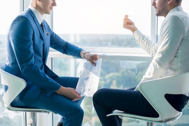 Homem negócios, tendo, conversa, com, seu, colega masculino, segurando, infographic, folha