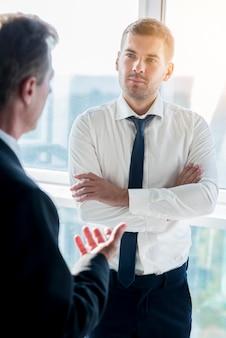 Homem negócios, tendo, conversa, com, seu, sócio masculino, em, escritório