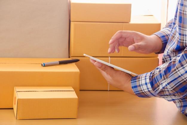 Homem negócios, trabalhando, com, telefone móvel, e, embalagem, marrom, pacotes, caixa, em, escritório lar