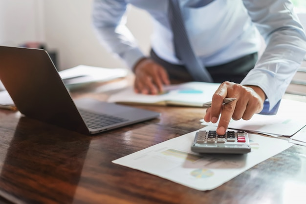 Homem negócios, trabalhando, escrivaninha, escritório, usando, um, calculadora, para, calcular, dinheiro, relatório