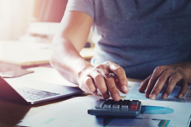 Homem negócios, trabalhando, escrivaninha, usando, calculadora, para, calcular, dados, de, finanças, em, escritório