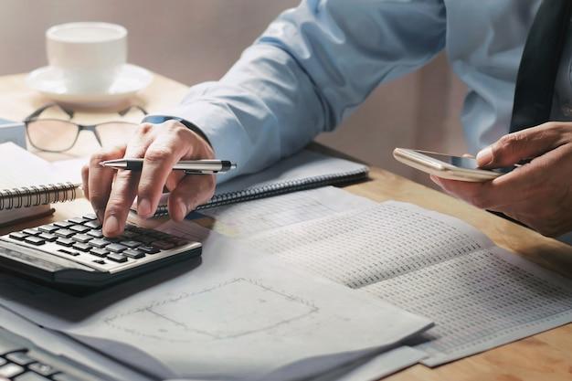 Homem negócios, trabalhar, escrivaninha, em, escritório, usando, calculadora, e, móvel