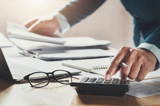 Homem negócios, usando, calculadora, para, calcule, trabalhando, em, escritório