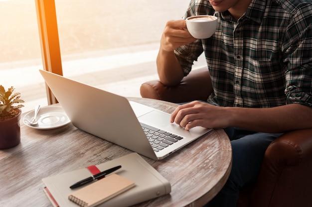 Homem negócios, usando computador portátil, com, tabuleta, e, caneta, ligado, tabela madeira, em, loja café, com, um, xícara café