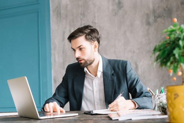 Homem negócios, usando computador portátil, e, fazendo anotações