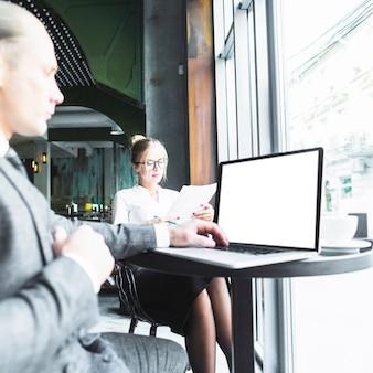 Homem negócios, usando computador portátil, enquanto, seu, colega, examinando, documentos, em, caf�