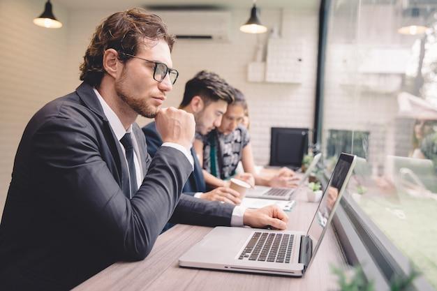 Homem negócios, usando computador portátil, enquanto, trabalhando, em, loja café