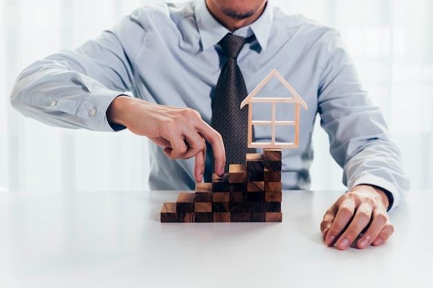 Homem negócios, usando, mão, para, subir, blocos, direção, casa