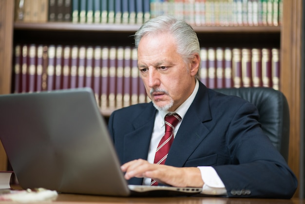 Homem negócios, usando, seu, laptop, em, um, biblioteca