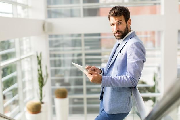 Homem negócios, usando, seu, tablete digital, em, escritório