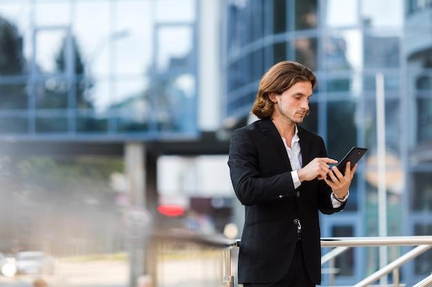 Homem negócios, usando, seu, tabuleta, ao ar livre