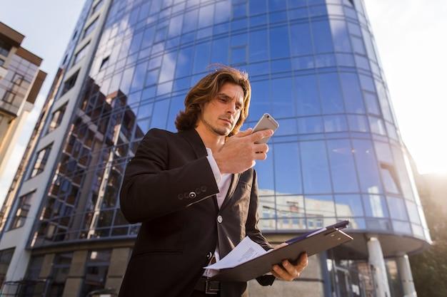 Homem negócios, usando, seu, telefone, frente, um, predios