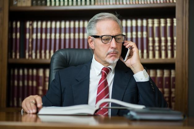 Homem negócios, usando, seu, telefone móvel, enquanto, leitura, seu, agenda