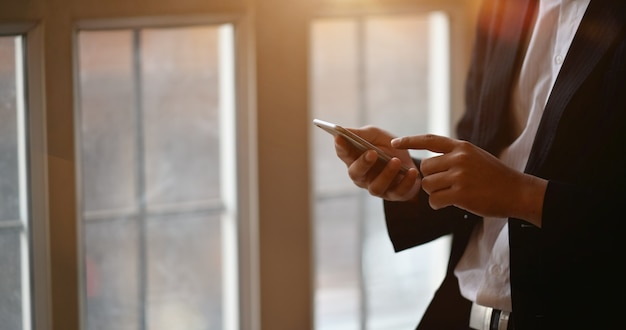 Homem negócios, usando, smartphone, em, escritório