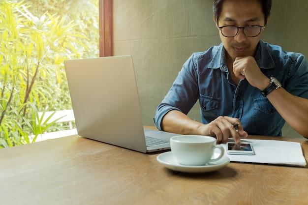 Homem negócios, usando, telefone pilha, com, laptop, e, xícara café, ligado, escrivaninha madeira