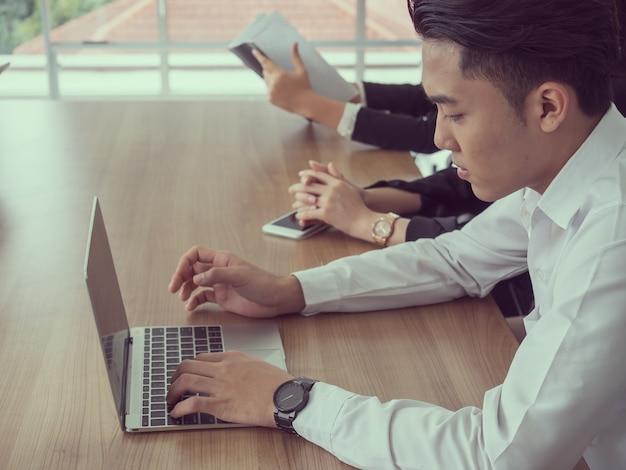 Homem negócios, use computador, em, metting, sala