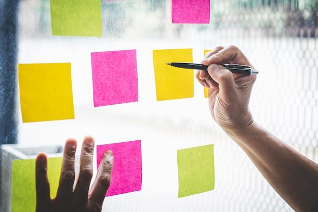 Homem negócios, uso, post-it, notas, para, planejando, idéia, e, marketing negócio, estratégia, nota pegajosa, ligado, parede