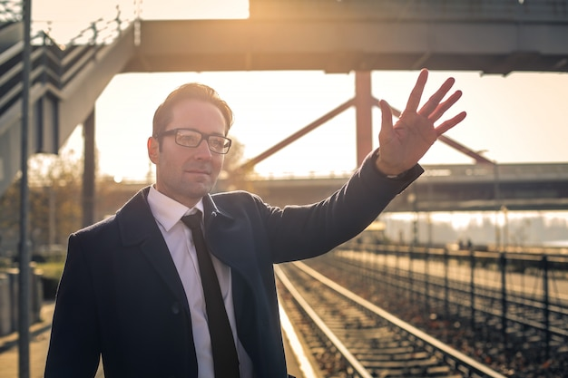 Homem negócios, waving, em, a, estação de comboios