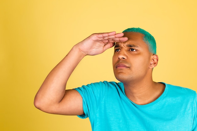 Homem negro africano casual em parede amarela olhando ao longe
