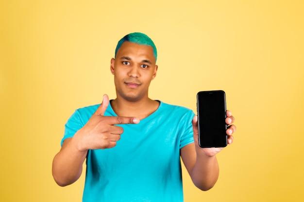Homem negro africano casual na parede amarela com o dedo indicador do ponto feliz positivo do celular na tela preta vazia