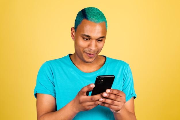 Homem negro africano casual na parede amarela com telefone celular e sorriso feliz, olhar na tela, ler mensagem de notícias