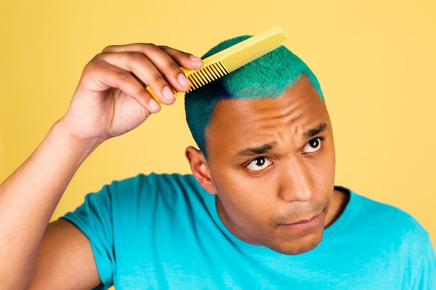 Homem negro africano casual na parede amarela escova de cabelo azul brilhante, conceito de salão de beleza