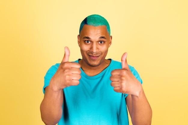 Homem negro africano casual na parede amarela feliz e positivo olhar para a câmera mostrar os polegares concordar