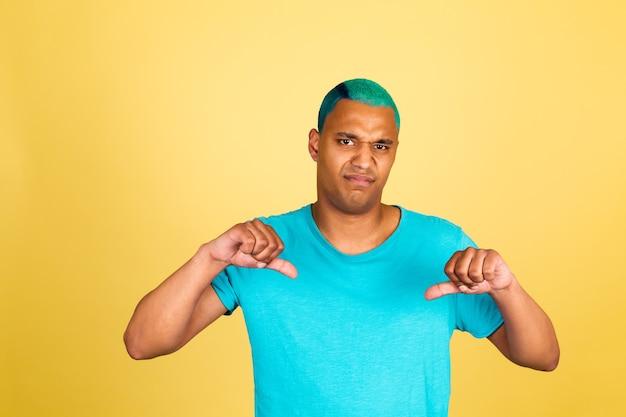 Homem negro africano casual na parede amarela infeliz não gostou ponto dois polegares para baixo olhar para a câmera
