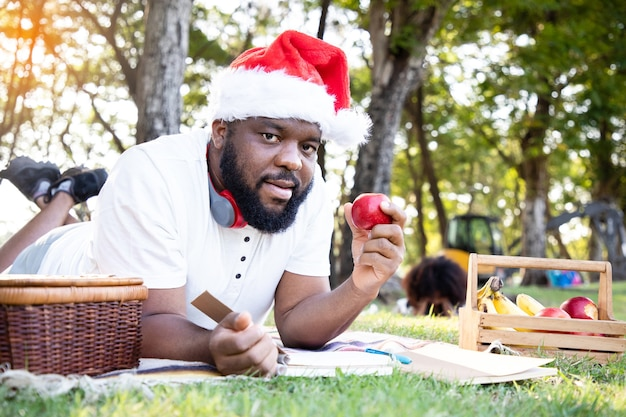 Homem negro africano com chapéu de papai noel e laptop para comunicação, trabalhando no jardim