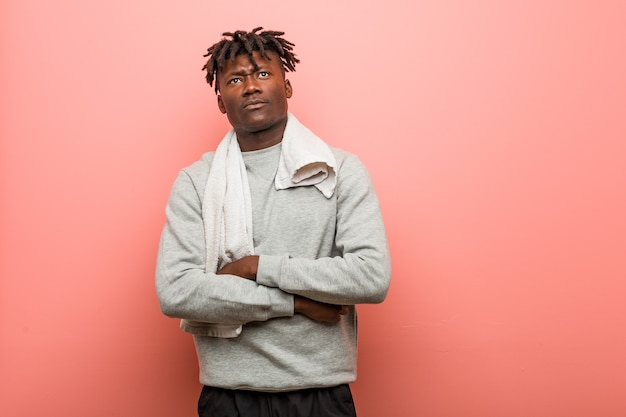 Homem negro africano de aptidão jovem infeliz com expressão sarcástica.
