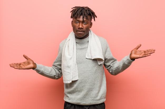 Homem negro africano de aptidão jovem mostrando uma expressão de boas-vindas.