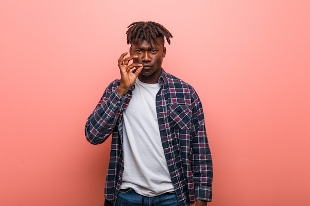 Homem negro africano novo com os dedos nos bordos que mantêm um segredo.