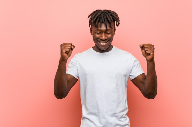 Homem negro africano novo que levanta o punho, sentindo feliz e bem sucedido. conceito de vitória.