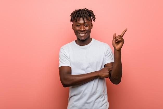 Homem negro africano novo que sorri alegremente apontando com dedo indicador afastado.