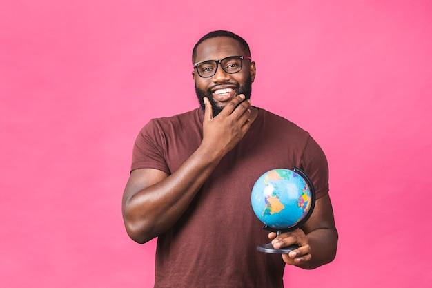 Homem negro afro-americano alegre segurando o globo com amor e carinho, isolado sobre o fundo rosa. conceito de viagens, à procura de uma jornada.