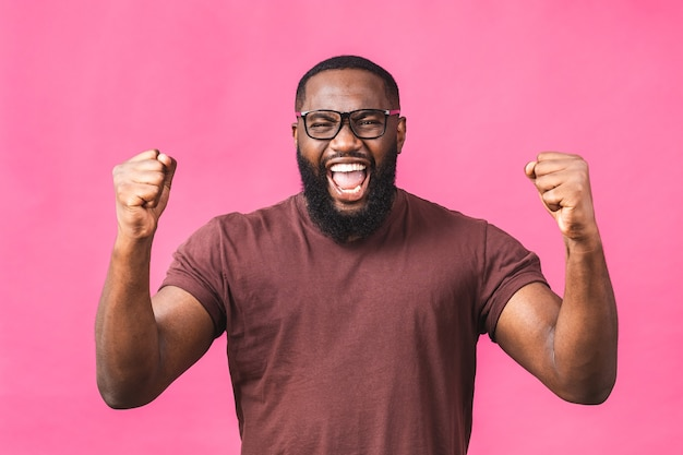 Homem negro afro-americano bonito alegre fazendo gesto de sim enquanto animado com a vitória. jovem fã em êxtase torcendo e expressando apoio. conceito de sucesso isolado sobre fundo rosa.