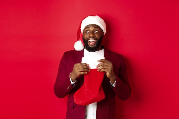 Homem negro alegre olhando o canto superior esquerdo e sorrindo, segurando uma meia de natal com presentes, em pé sobre um fundo vermelho
