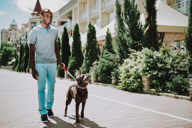 Homem negro andando com cachorro no parque.